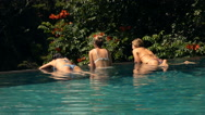Girls relaxing on the edge of swimming pool, super slow motion Stock Footage
