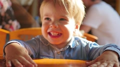 The beautiful child at the table having fun playing Stock Footage