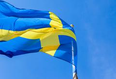 Flag of Sweden waving in the wind on a blue sky background Stock Photos