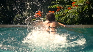 Young woman relaxing on edge of swimming pool, slow motion Stock Footage