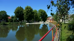 Pond in the village with trees - building in the background - sunny day Stock Footage
