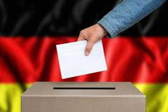 Election in Germany. The hand of woman putting her vote in the ballot box. Ge Stock Photos