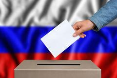 Election in Russia. The hand of woman putting her vote in the ballot box. Rus Stock Photos