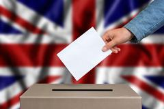 Election in Great Britain. The hand of woman putting her vote in the ballot b Stock Photos