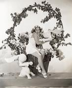 Woman sitting in giant Easter basket with toy rabbits Kuvituskuvat