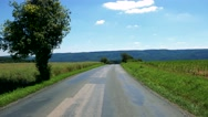 Road in the countryside between fields with trees - sunny day Stock Footage