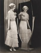 Woman in tiered dress looking at her reflection in mirror Stock Photos