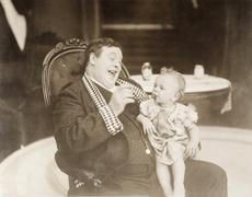 Man laughing at baby smoking cigar Stock Photos