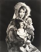 Women wearing Eskimo fur coat holding dolls Stock Photos