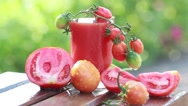 Juicy ripe red tomatoes and fresh tomato juice in a glass Stock Footage