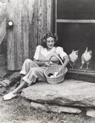 Woman collecting eggs from chickens Stock Photos