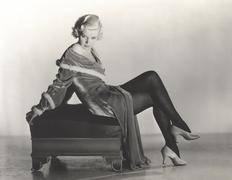 Woman in velvet dress sitting on footstool Stock Photos