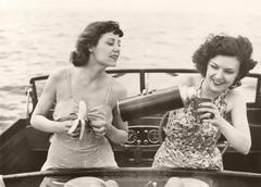 Two women having a snack on motorboat Stock Photos