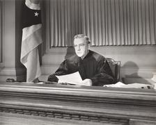Judge holding a document in courtroom Stock Photos