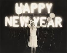 Woman standing in front of neon Happy New Year sign Stock Photos