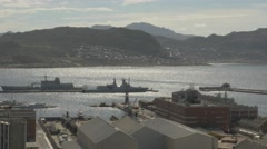4k Speed Boat Sailing By Naval Ships At Dockyard Pier Mountains In Background Stock Footage