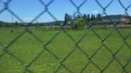 Shot over plastic fence on meadow with grass - steadicam move Stock Footage