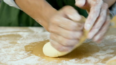 Woman kneading the dough for the bread on the wooden table, dolly shot Stock Footage