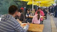 People sit at tables eating dishes at street food festival Stock Footage