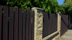 Wood fence with bushes - shot from street - steadicam move Stock Footage