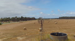 AERIAL: Flying above golden field of bales on old fashioned windmill farm Stock Footage