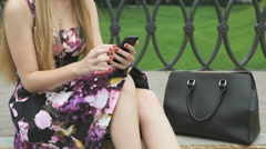Girl holding a smartphone in the park outdoors Stock Footage