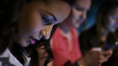 Female friends sitting next to each other engrossed in their electronic devices Stock Footage