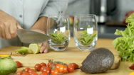 Woman cutting lime into slices and adding it into glasses, dolly shot Stock Footage