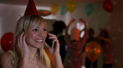 4K Happy girl trying to talk on phone at noisy house party Arkistovideo