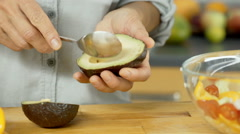 Woman peels avocado from skin and cutting it on the wooden board, dolly shot Stock Footage