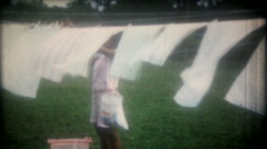 Black housewife hangs laundry on clothesline 3629 -vintage film home movie Stock Footage