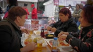 Old women aged senior people eat at street food festival communicate sit table Stock Footage