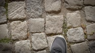 Man legs in dark sneakers walk the pavement street - upper POV camera slow Stock Footage