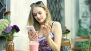 Girl texting on smartphone in the outdoor cafe and smiling to the camera Stock Footage