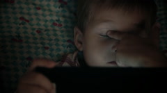 Close-up of kid face looking at tablet computer at night Stock Footage