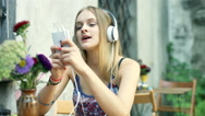 Girl smiling to the camera while listening music and texting on smartphone Stock Footage