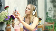 Girl doing selfies on smartphone while listening music in the outdoor cafe Stock Footage