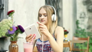 Girl connecting headphones to tablet and start listening music Stock Footage