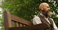 4K Portrait bearded man relaxing in the park & smoking electronic cigarette Stock Footage