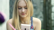 Pretty, blonde girl sitting in the outdoor cafe and texting on smartphone Stock Footage