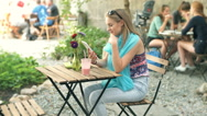 Girl browsing internet on tablet and smiling to the camera in the outdoor cafe Stock Footage