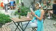 Girl connecting headphones to tablet and playing some music Stock Footage