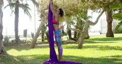 Female acrobat working outdoors on silk ribbons Stock Footage