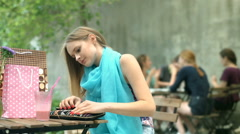 Girl taking cellphone from the bag and chatting with someone in the outdoor cafe Stock Footage
