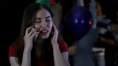 4K Happy girl trying to talk on phone at noisy house party Stock Footage
