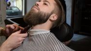 Hairdresser with tattoo serving client in barbershop Stock Footage