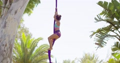 Gorgeous young woman gymnast working out on silks Stock Footage