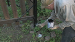 Gardener painting the iron fence using black paint Stock Footage