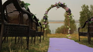 There is wedding arch with flowers on lake or river shore Stock Footage