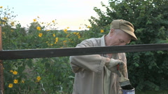 Aged man 60s paints the iron fence using a black Stock Footage